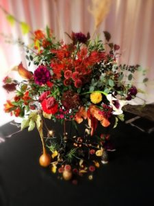 Orange and burgundy autumnal floral table centrepiece high angle