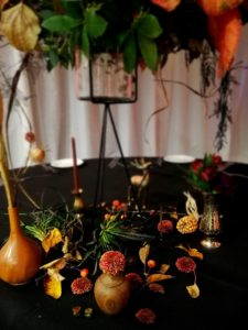 Black table decorated with small wooden vases filled with autumnal flowers and foliage