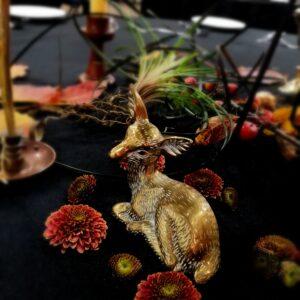 Brass deer ornament and flower heads sprinkled on black tablecloth