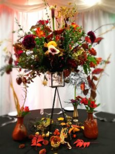 Orange and burgundy autumnal floral table centrepiece